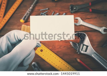 house construction and repair services - worker holding blank business card over work tools on wooden background