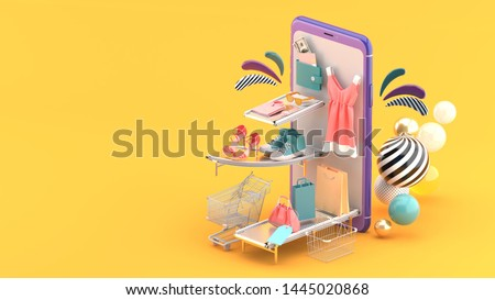 The fashion house on the smartphone is surrounded by colorful balls on a orange background.-3d rendering.