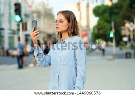 woman stands on the street and looks into the phone #1445060576