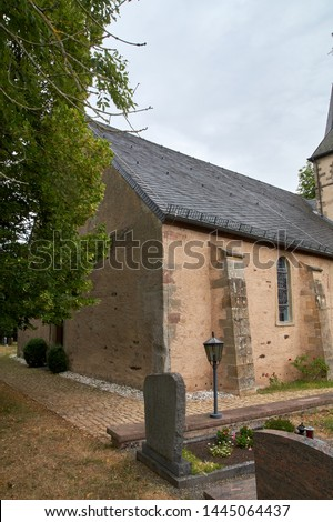 Church of St. Peter in Roth an der Our, Germany - a former church of the Knights Templar, partial summer exterior view under dramatic overcast sky #1445064437