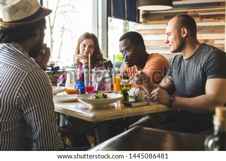 A company of multicultural young people in a cafe eating pizza, drinking cocktails, having fun #1445086481