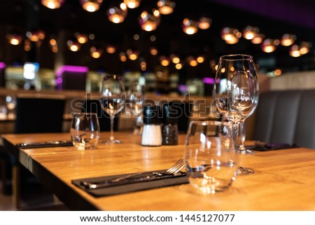 beautifully laid tables with glasses and appliances at night in restaurant #1445127077