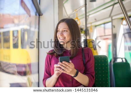Young woman passenger standing with  smartphone while moving in the modern tram, enjoying trip at the public transport #1445131046