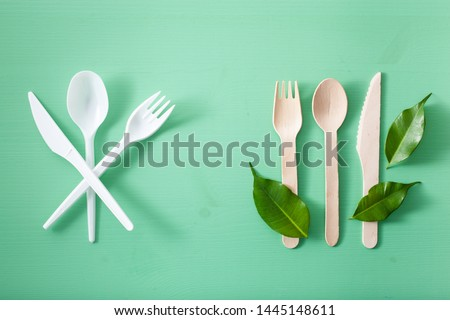harmful plastic cutlery and eco friendly wooden cutlery. plastic free concept Royalty-Free Stock Photo #1445148611
