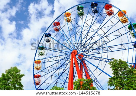 Giant ferris wheel against blue sky and white cloud which mean an amusement-park or fairground ride consisting of a giant vertical revolving wheel with passenger cars suspended on its outer edge #144515678