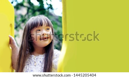 Portrait of beautiful young girl on the playground. Royalty-Free Stock Photo #1445205404