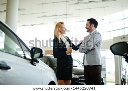 Dealer showing a new car model to the potential customer #1445220941