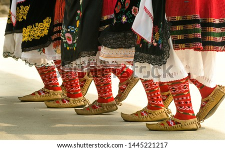 Bulgarian folklore. Girls dancing folk dance. People in traditional costumes dance Bulgarian folk dances. Close-up of female legs with traditional shoes, socks and costumes for Bulgarian folk dances. #1445221217