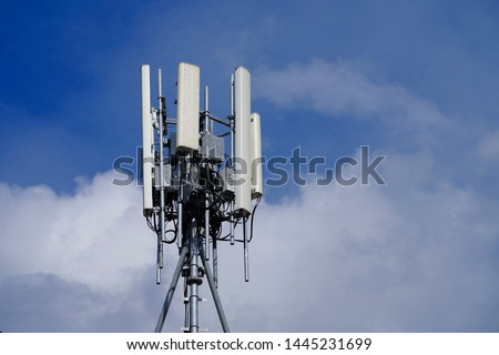Telecommunication tower of 4G and 5G cellular. Macro Base Station. 5G radio network telecommunication equipment with radio modules and smart antennas mounted on a metal on cloulds sky background. Royalty-Free Stock Photo #1445231699