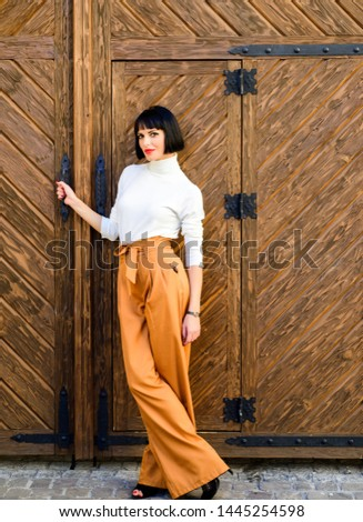 High waisted trousers. Woman attractive brunette wear fashionable clothes. Femininity and emphasize feminine figure. Girl wear loose high waisted pants. Fashion shop. High waisted pants fashion trend. #1445254598