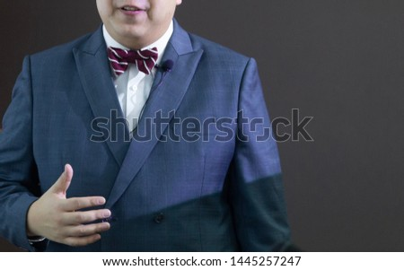 The male speaker with the lavaliere microphone, bow tie and suit is doing the public speaking under the spotlight with grey background.