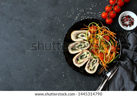 Chicken stuffed with ham, spinach and cheese served with fresh salad on dark background. Top view with copy space. #1445314790