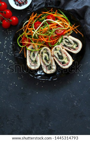 Chicken stuffed with ham, spinach and cheese served with fresh salad on dark background. Top view with copy space. #1445314793