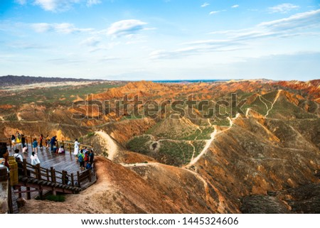 Mingsha Mountain Scenic Spot, Dunhuang City, Gansu Province, China—July 7th, 2019: Visitors stand on the observation deck on the mountain and look at the boundless Yadan landscape. #1445324606