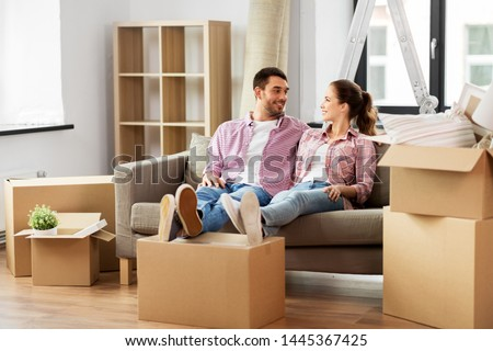moving, people, repair and real estate concept - happy couple with cardboard boxes sitting on sofa at new home #1445367425