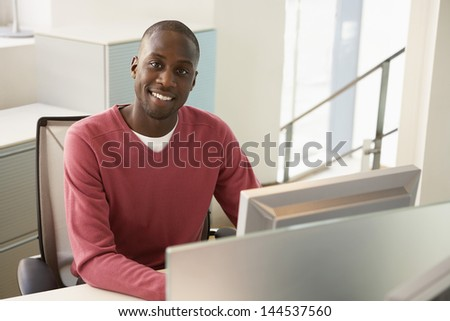 Portrait of happy African American businessman sitting at computer desk #144537560