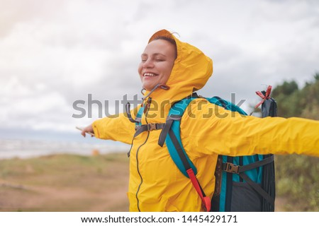 happy young beautiful woman in a yellow jacket windbreaker with a hiking backpack on the shore of the North Sea Royalty-Free Stock Photo #1445429171