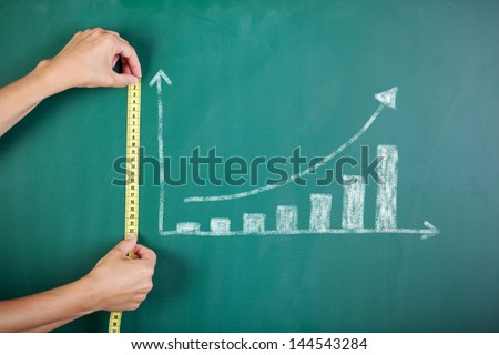 Closeup of woman's hands measuring bar graph with tape on blackboard Royalty-Free Stock Photo #144543284