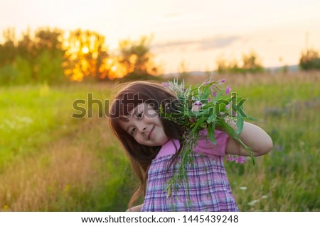 Little happy girl with flowers on a background of green sunny meadow #1445439248