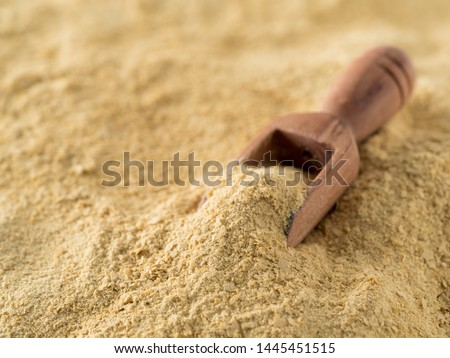 Nutritional yeast background. Nutritional inactive yeast with small wooden scoop. Copy space. Nutritional yeast is vegetarian superfood with cheese flavor, for healthy diet #1445451515