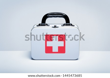 Tin first aid kit with cross emblem on grey background #1445473685