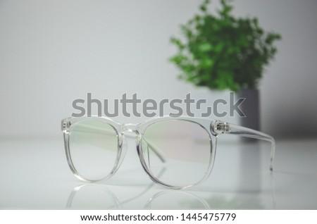Transparent glasses with transparent plastic rim on white table #1445475779