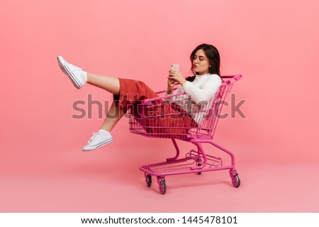 Stylish teen girl in culottes and white sweater sits in supermarket trolley. Model in glasses sends kiss and makes selfie on pink #1445478101