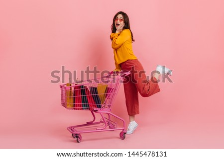 Surprised girl in pink culottes posing with trolley full of multi-colored packages with new clothes #1445478131
