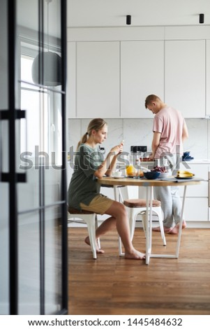 Young woman sitting by table in the kitchen, having breakfast and using smartphone while her husband cooking #1445484632
