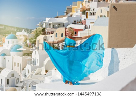 Beautiful woman in dress against  architecture of Santorini island, Greece #1445497106