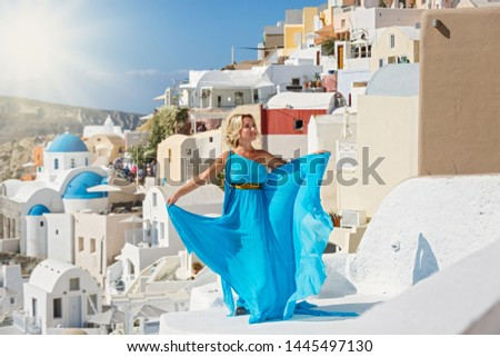 Beautiful woman in dress against  architecture of Santorini island, Greece #1445497130