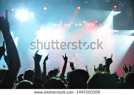 A crowd of people dancing at a musical rock concert under the light and smoke of spotlights #1445503208