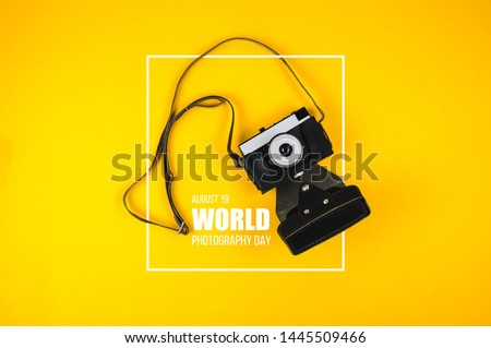 "Old camera and text ""World photography day"" on yellow background"