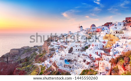 Charming sunset view of traditional Greek village Oia on Santorini island in Greece. Santorini is iconic travel destination in Greece, famous of its sunsets and traditional white and blue architecture #1445550260