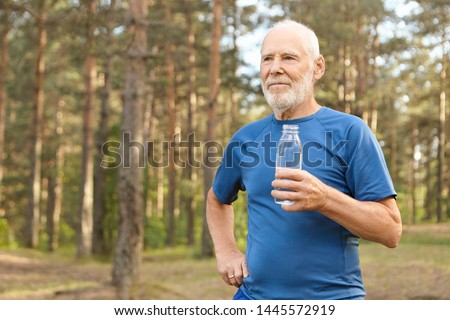 Portrait of handsome tired European senior elderly male in t-shirt holding glass bottle, enjoying fresh drinking water after running exercise in forest, catching his breath, looking around #1445572919