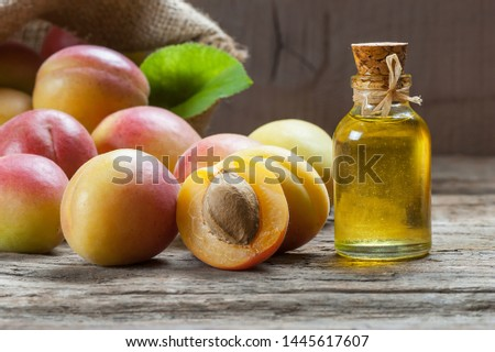 Glass bottle of Apricot seed kernel oil ( prunus armeniaca oleum ) with fresh ripe apricot fruits on wooden rustic background #1445617607
