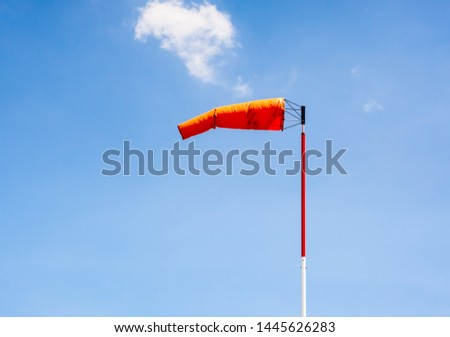 Windsock on pole pointing left in breeze against blue sky. #1445626283