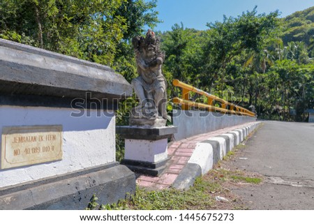 Bridge with yellow metal railing over river in mountains on Bali island. Decorative stone statues represent mythological protectors. In the background wild tropical vegetation and mountain range. #1445675273
