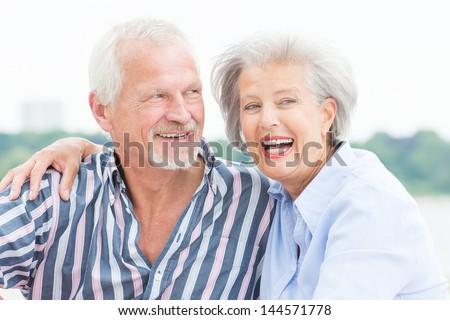 Portrait from a happy senior couple in front of cloudy sky #144571778