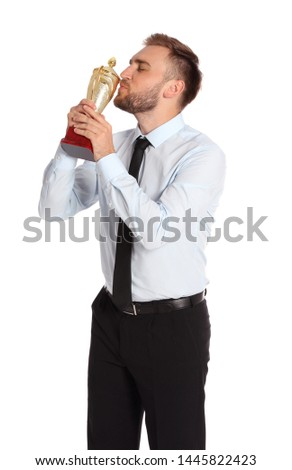 Portrait of happy young businessman kissing gold trophy cup on white background #1445822423