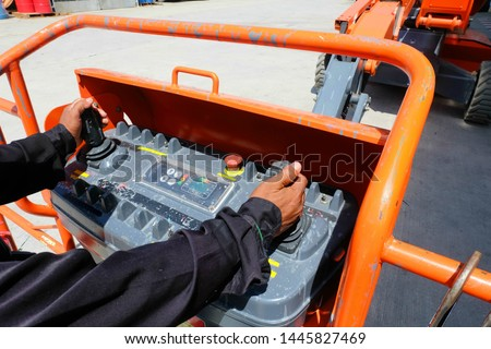 Workers are use control panel to driving the Orange articulate boom lift or telescopic boom lifts and bucket crane mounted on truck to safety for working at heights and articulating boom lift. #1445827469