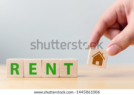 Hand holding wood cube block with icon house and word RENT. Property investment and house mortgage financial concept #1445861006