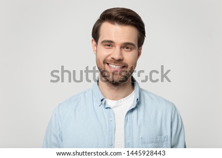 Head shot portrait smiling attractive confident millennial man wearing blue shirt posing on grey studio background, guy with bristle having white toothy smile advertise dental services or procedure #1445928443
