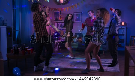 At the College House Party: Diverse Group of Friends Have Fun, Dancing and Socializing. Boys and Girls Dance in the Circle. Disco Neon Strobe Lights Illuminating Room. #1445942390