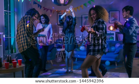 At the College House Party: Diverse Group of Friends Have Fun, Dancing and Socializing. Boys and Girls Dance in the Circle. Disco Neon Strobe Lights Illuminating Room. #1445942396