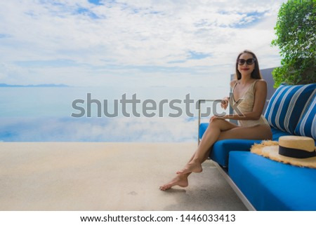 Portrait young asian woman relax smile happy around swimming pool in hotel and resort for holiday vacation travel concept #1446033413