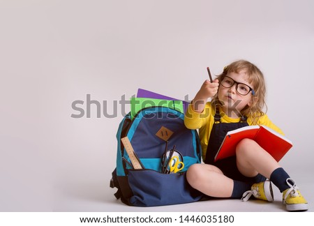 Children go back to school. Little girl doing homework at home with backpack. Pupil of primary school learn to write and read. Child is reading a book, writing and painting. Kindergarten or preschool  #1446035180