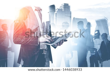 Unrecognizable businessman with laptop and his colleague silhouettes over cityscape background. Concept of teamwork and business lifestyle. Toned image double exposure #1446038933