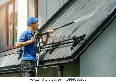 man standing on ladder and cleaning house metal roof with high pressure washer Royalty-Free Stock Photo #1446080288