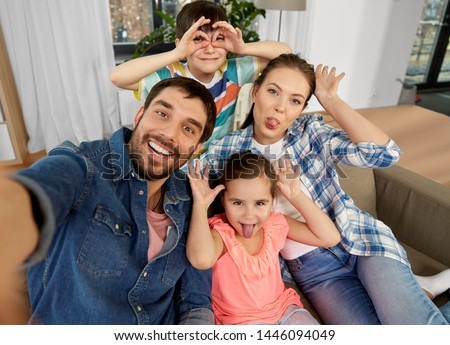 family, fun and people concept - happy father, mother, little son and daughter taking selfie and making faces at home